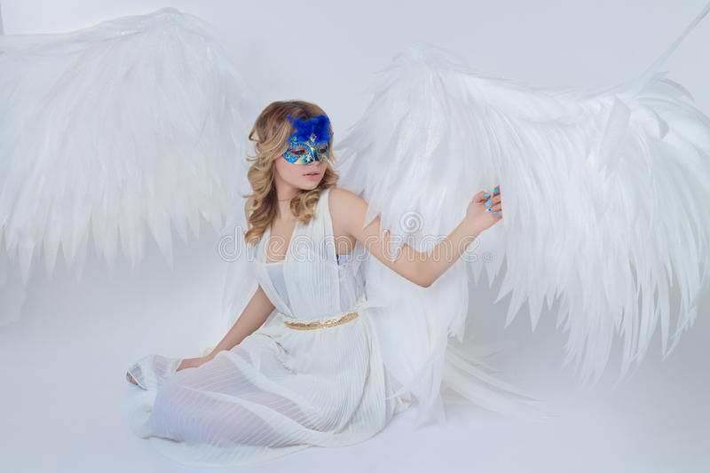 Beautiful young model with big angel wings sitting in the studio royalty free stock photo
