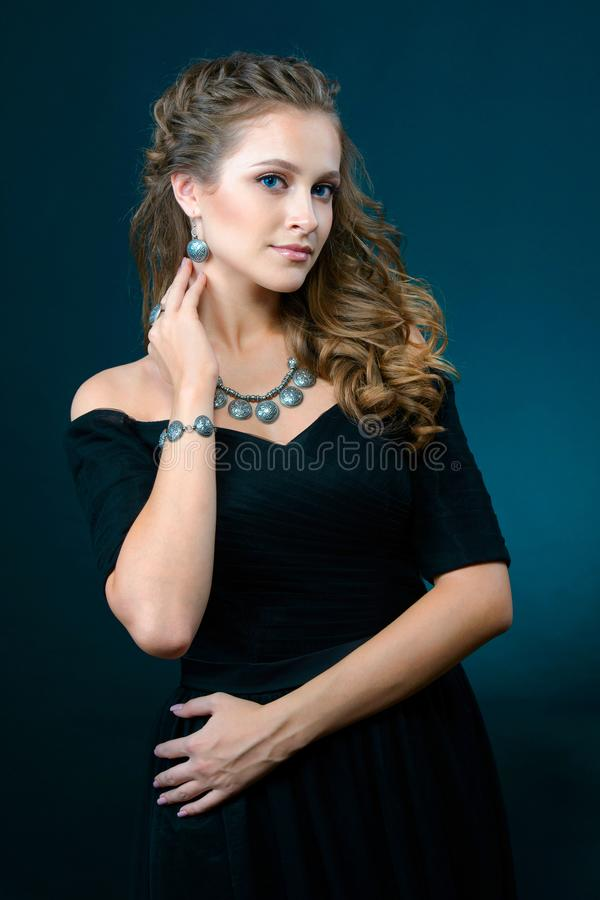 Beautiful young model with earrings necklace and ring on dark ba stock images