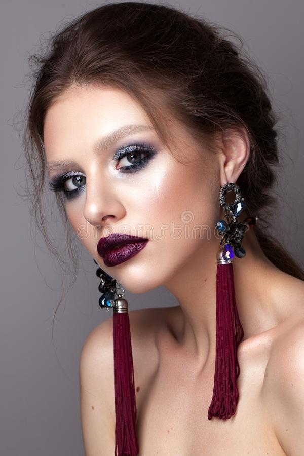 Beautiful young model with professional makeup, perfect skin, long earrings, dark lips. Colorful make up royalty free stock photography