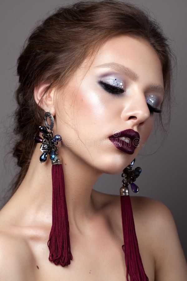 Beautiful young model with professional makeup, perfect skin, long earrings, dark lips. Colorful make up. Closed eyes stock image