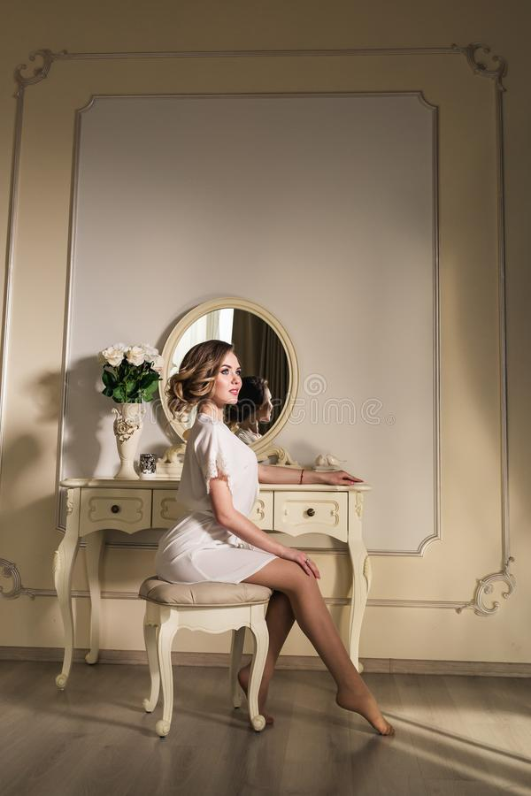 A beautiful young model is sitting on a chair near a boudoir table. royalty free stock photo
