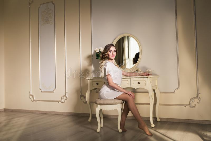 A beautiful young model is sitting on a chair near a boudoir table. stock photos