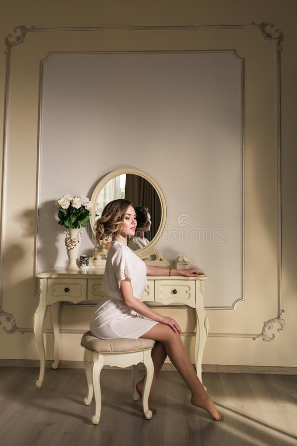 A beautiful young model is sitting on a chair near a boudoir table. stock images