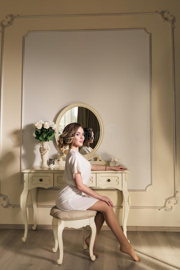 A beautiful young model is sitting on a chair near a boudoir table. stock photography