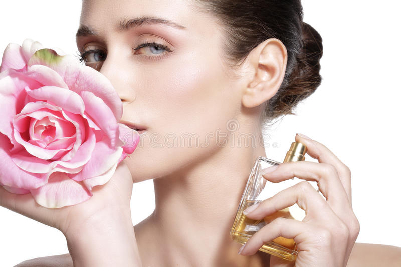 Beautiful young model spraying a flowers fragrance on her body. On white stock photo