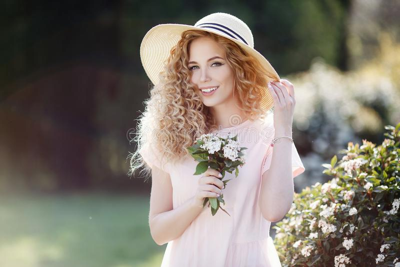 Attractive young woman in a straw hat alone in a blooming spring park stock images
