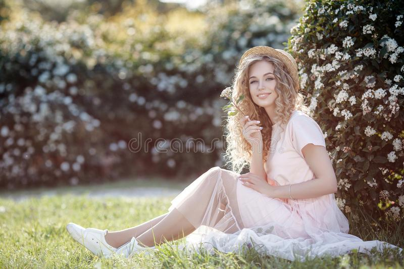 Attractive young woman in a straw hat alone in a blooming spring park stock photo