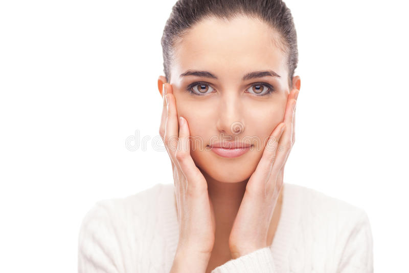 Beautiful young model touching her skin. Beautiful female model touching her smooth glowing face skin and smiling at camera stock photography
