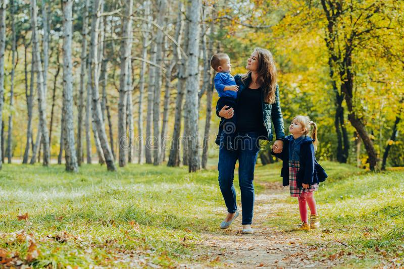Mom with daughter and son are walking in the autumn park. Family for a walk in the forest royalty free stock images