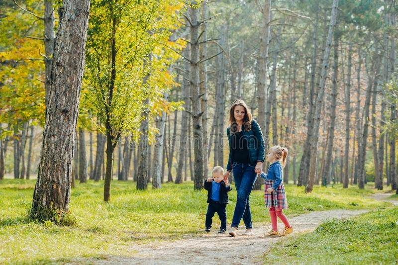Mom with daughter and son are walking in the autumn park. Family for a walk in the forest royalty free stock image