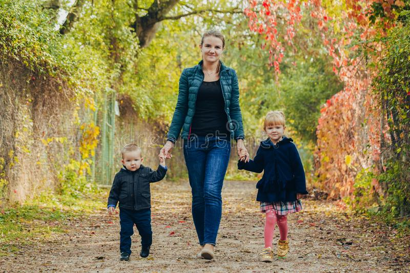 Mom with daughter and son are walking in the autumn park. Family for a walk in the forest stock photos