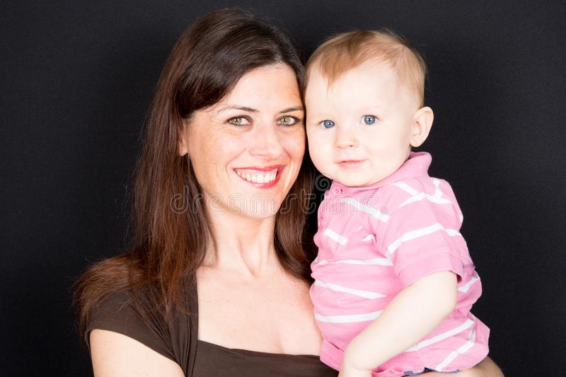Beautiful young mom and her sweet little baby son looking at camera and smiling stock photography