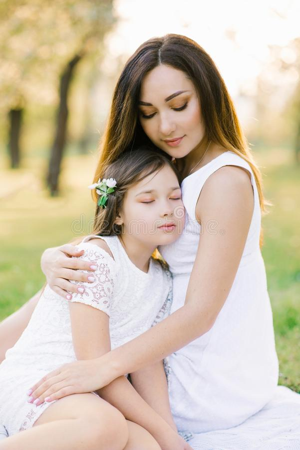 Beautiful young mom hugs her daughter. Mom and daughter in white dresses on a picnic stock photos