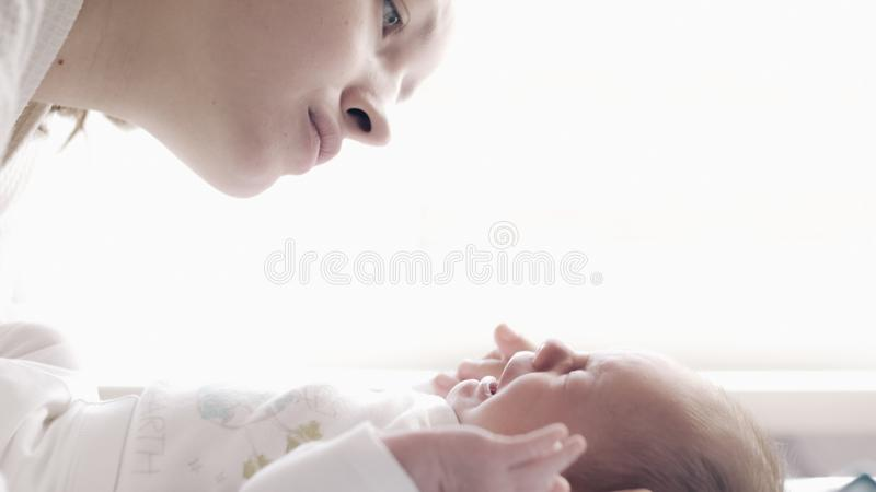 Beautiful young mother with crying baby stock photo