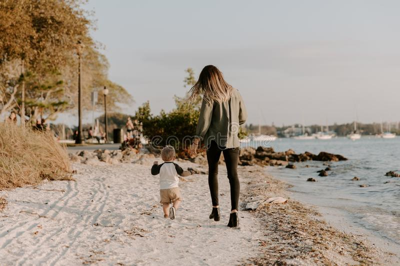 Beautiful Young Mother and Cute Little Boy Son Walking and Enjoying the Nice Outdoor Weather on the Sandy Beach next to the Ocean royalty free stock photos
