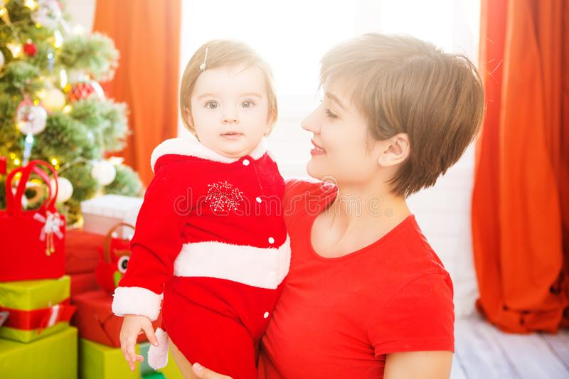 Beautiful young mother and daughter dressed as santa claus enjoying a Christmas day royalty free stock photos