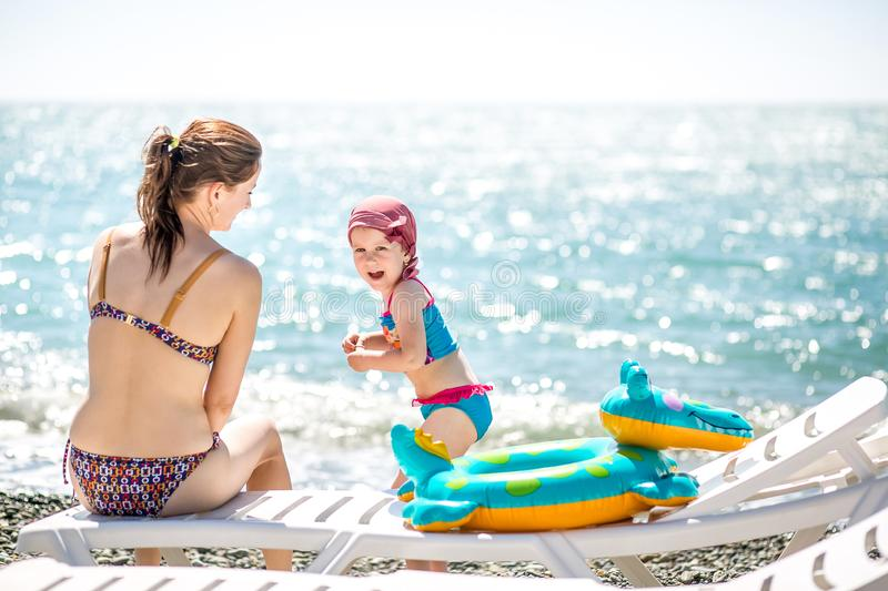 Beautiful young mother and daughter having fun resting on the sea. They sit on the beach with pebbles on a deck chair, little girl stock photo