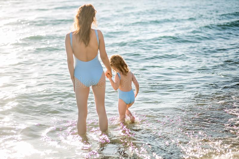 Beautiful young mother and daughter having fun resting on the sea. They stand in the water in the same swimsuit, back in the frame. Horizontal photo stock image