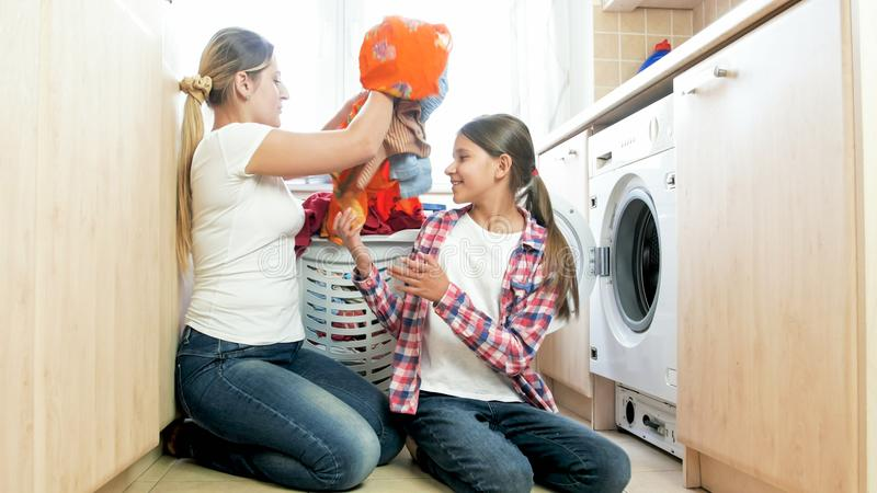 Beautiful young mother with daughter loading clothes in washing machine at laundry stock photos