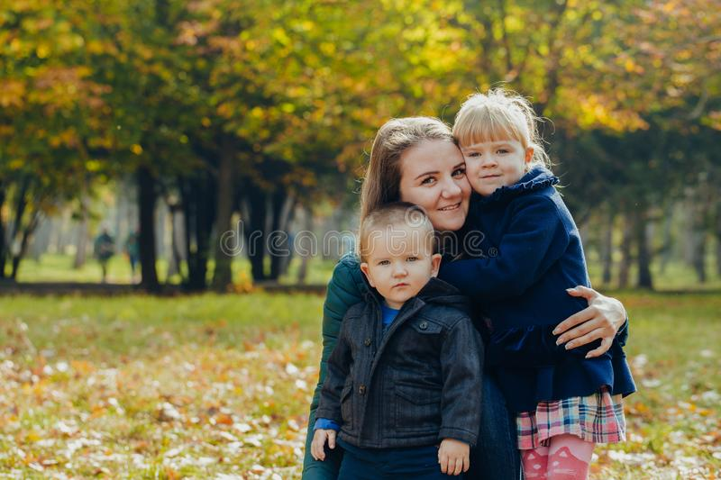 Beautiful young mother with daughter and son are walking in the autumn park. close-up portrait stock photos