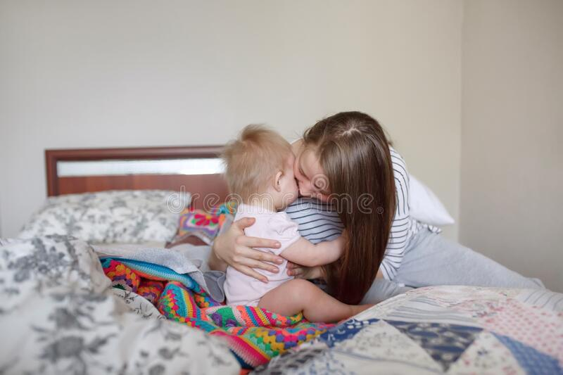 Beautiful young mother embracing and comforting her little baby infant in the morning. Beautiful young mother embracing and comforting her little baby infant on royalty free stock photos