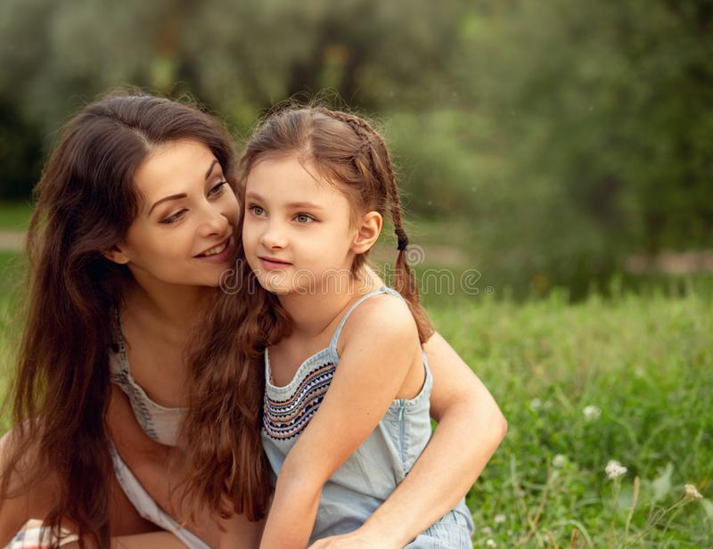 Beautiful young mother embracing her cute long hair daughter on summer green grass background in sunny day. Portrait of love royalty free stock photo
