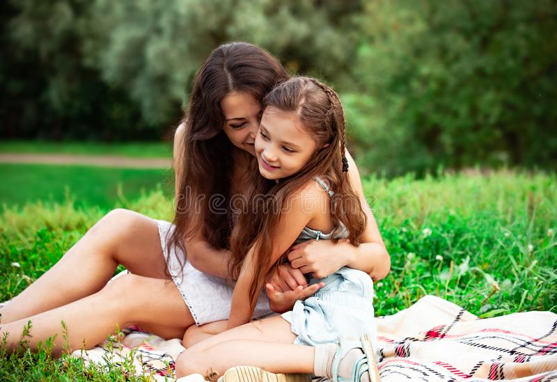 Beautiful young mother embracing and kissing her cute long hair daughter on summer green grass background royalty free stock photo