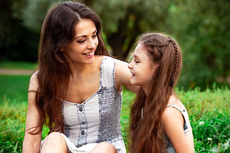 Beautiful young mother embracing and talking with her cute long hair daughter on summer green grass background in sunny day royalty free stock photos