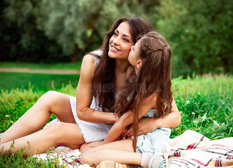 Beautiful young mother embracing and talking with her cute long hair daughter on summer green grass background in sunny day stock photo