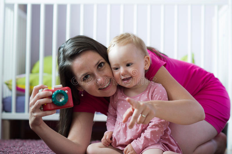 Beautiful young mother with her cute baby daughter posing royalty free stock photos