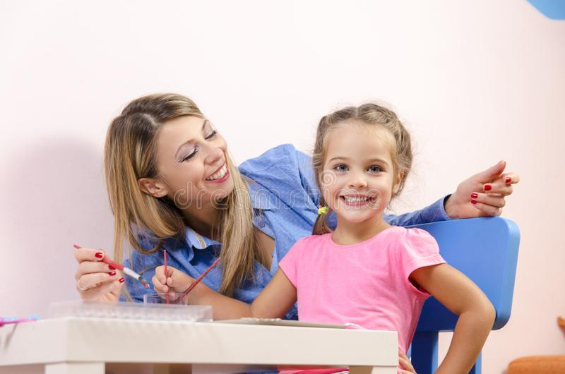 Beautiful young mother with her cute daughter drawing stock images