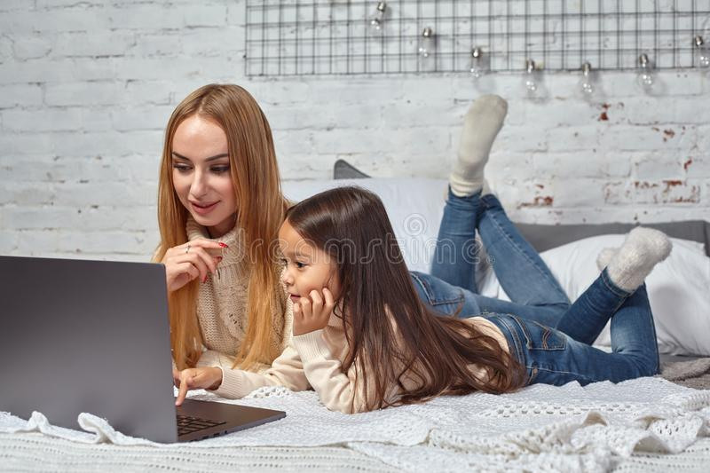 Beautiful young mother and her cute daughter in white sweaters and jeans lying on the bed at home, laughing and looking royalty free stock photo