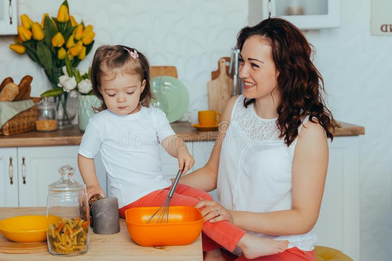 Attractive young woman and her little cute daughter are cooking on kitchen royalty free stock photos