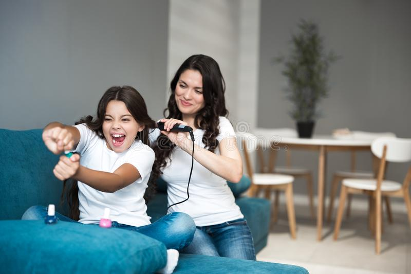 Beautiful young mother with her cute teen daughter having beauty day applying nail polish and curling hair using curler. Both looking happy royalty free stock images