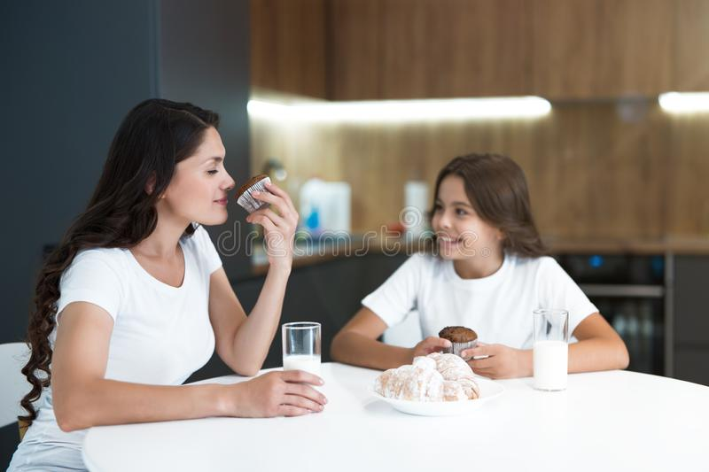 Beautiful young mother with her cute teenager daughter eating cupcakes and croissants for breakfast in the kitchen stock photos