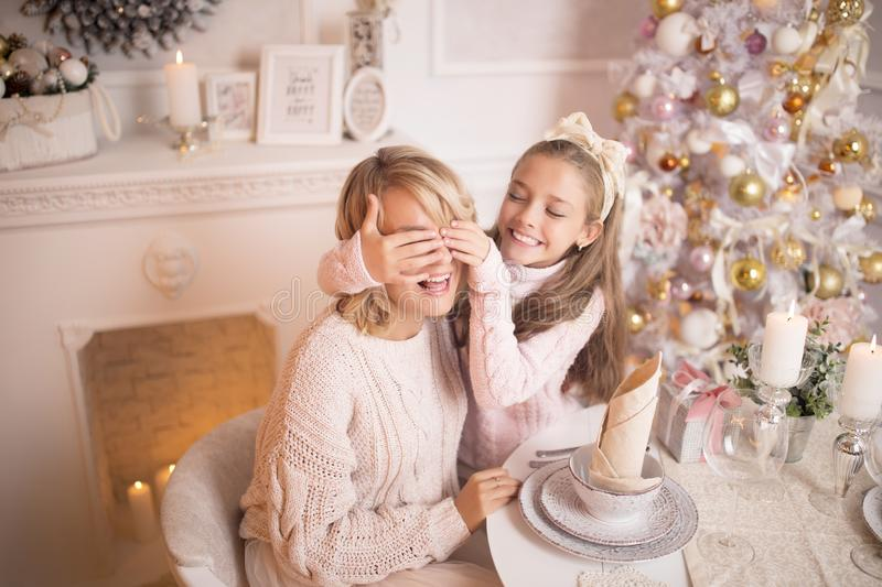 Beautiful young mother with her daughter in the New Year`s interior at the table near the Christmas tree. royalty free stock photos