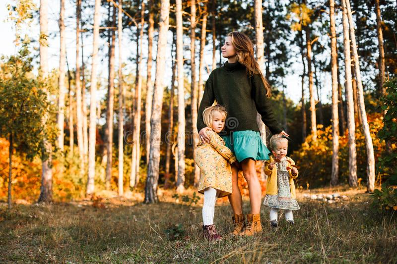Beautiful young mother and her little daughter walking in summer park. Woman and cute kid girl spending time together royalty free stock photo