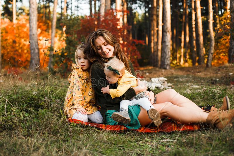 Beautiful young mother and her little daughter walking in summer park. Woman and cute kid girl spending time together stock photo