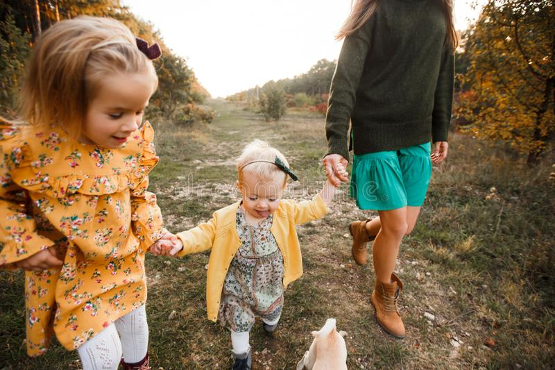 Beautiful young mother and her little daughter walking in summer park. Woman and cute kid girl spending time together royalty free stock image