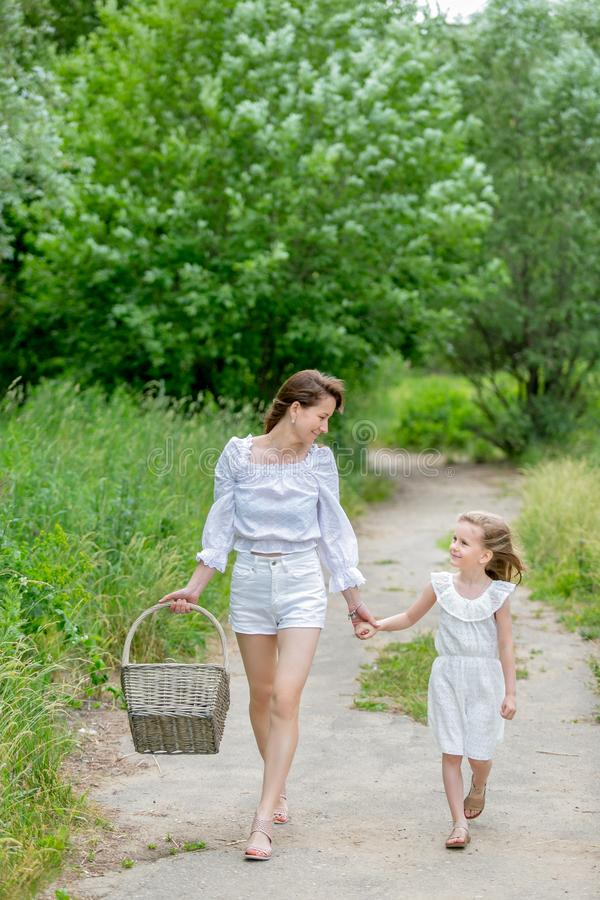 Beautiful young mother and her little daughter in white dress having fun in a picnic. They hold hands and look at each other, walk royalty free stock photography