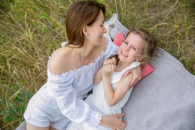 Beautiful young mother and her little daughter in white dress having fun in a picnic. They are lying on a plaid on the grass and royalty free stock images