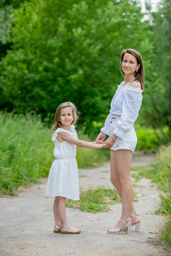 Beautiful young mother and her little daughter in white dress having fun in a picnic. They stand on a road in the park, holding royalty free stock photo