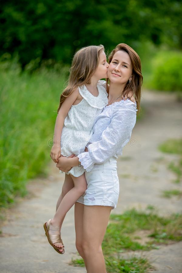 Beautiful young mother and her little daughter in white dress having fun in a picnic. They stand on a road in the park, mom holds stock photos