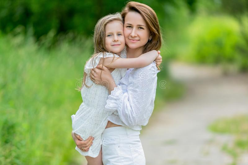 Beautiful young mother and her little daughter in white dress having fun in a picnic. They stand on a road in the park, mom holds royalty free stock photos