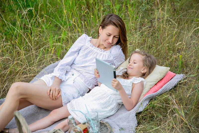 Beautiful young mother and her little daughter in white dress having fun in a picnic on a summer day. They lie on the rug and read royalty free stock images