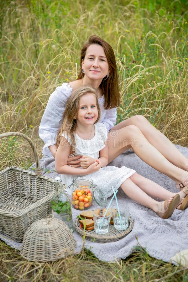 Beautiful young mother and her little daughter in white dress having fun in a picnic on a summer day. They sit on the rug and stock photo