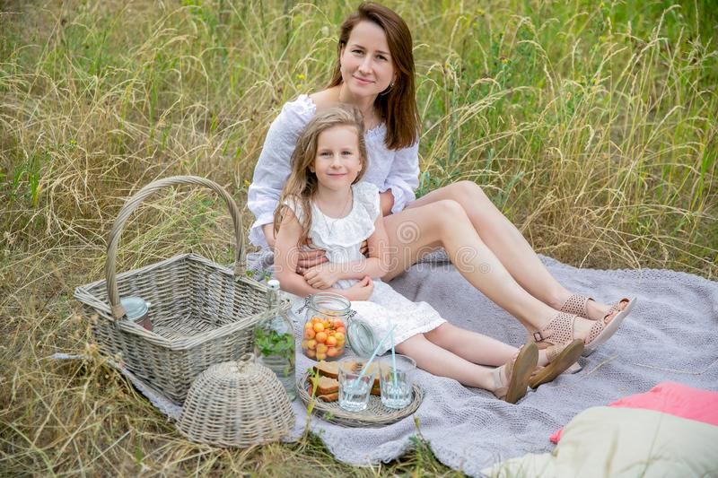 Beautiful young mother and her little daughter in white dress having fun in a picnic on a summer day. They sit on the rug and stock photography