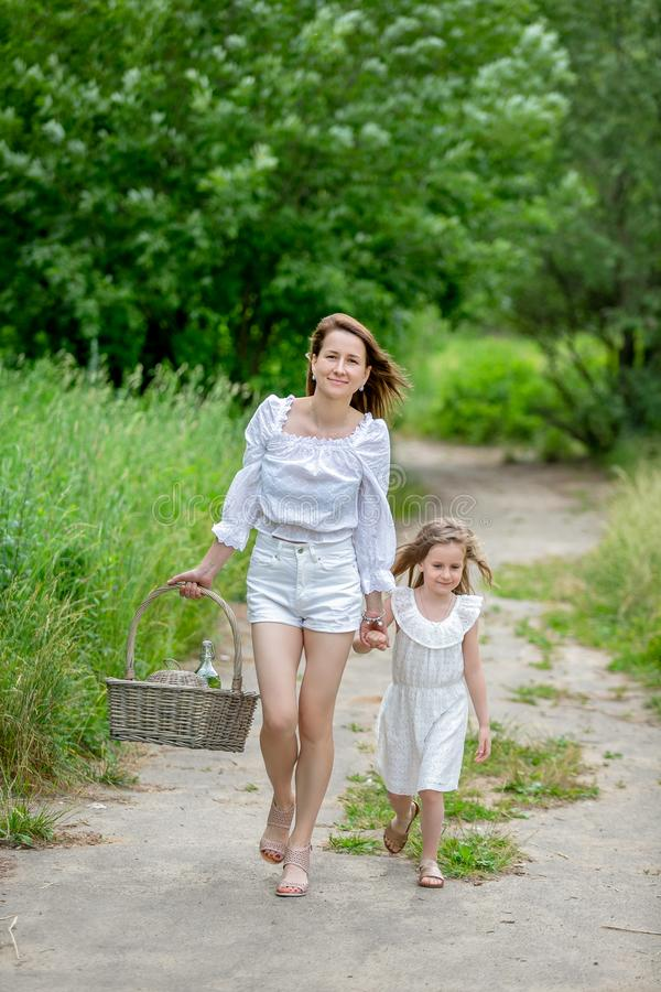 Beautiful young mother and her little daughter in white dress having fun in a picnic. They walk along the road in the park. stock images