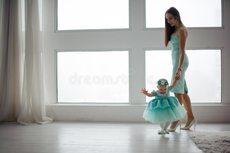 Beautiful young mother hold her daughter hand and walking in the room royalty free stock photography