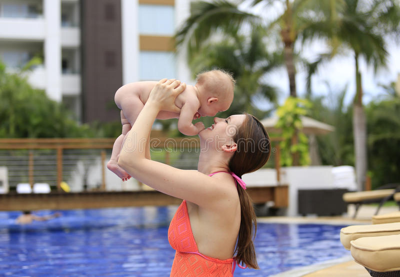 Beautiful young mother is holding baby girl outside near pool. Beautiful young mother is holding baby girl outside near fountain rock wall royalty free stock photography